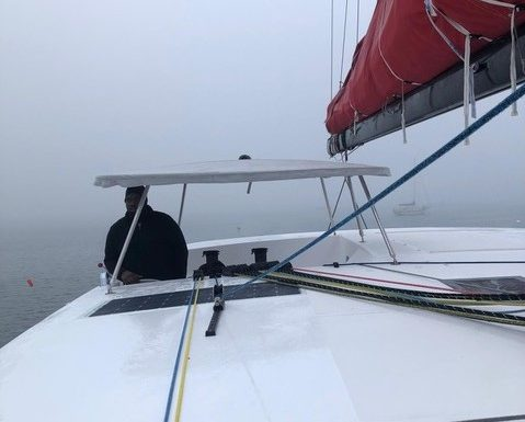 Cpt. Karl Reed looks out from the cockpit. The sea is misty and Karl is wrapped up in a fleece and hat